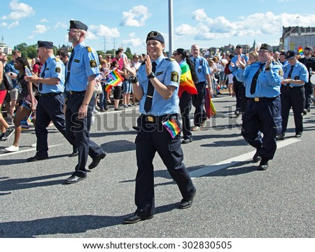 STOCKHOLM - AUG - 01. Stockholm Pride parade crossing the street with the name Skeppsbron 1 August 2015. Participation of police officers in carnival parade. - stock photo