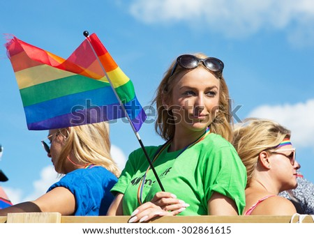 STOCKHOLM - AUG - 01. Stockholm Pride parade crossing the street with the name Skeppsbron 1 August 2015. Young woman with rainbow flag. - stock photo