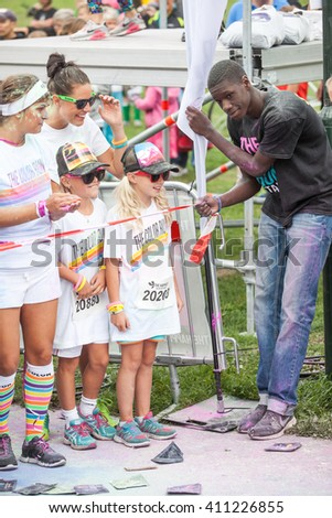 STOCKHOLM, AUGUST 2014, girls at different ages waiting at the starting line for the Color Run event. Volunteer making sure everybody is waiting behind the line. - stock photo