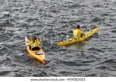 STOCKHOLM - JUL 02, 2016: Yellow canoes with officials before the start signal in the Women's ITU World Triathlon series event July 02, 2016 in Stockholm, Sweden