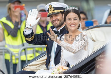 STOCKHOLM - JUN 13, 2015: Prince Carl-Philip and Princess Sofia laughing and waving in the royal carriage after the wedding with the crowd cheering. - stock photo