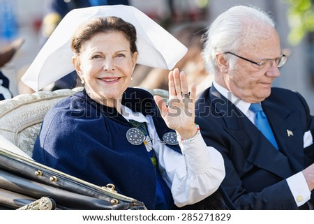 STOCKHOLM - JUN 06, 2015: Queen Silvia Bernadotte with King Carl XVI Gustaf of Sweden waiving to audience on their way to celebrate swedish national day. - stock photo
