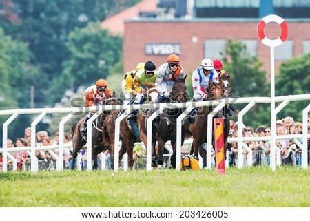 STOCKHOLM - JUNE 6: Group of jockeys fight to take the lead into the last curve at the Nationaldags Galoppen at Gardet with the crowd behind. June 6, 2014 in Stockholm, Sweden. - stock photo
