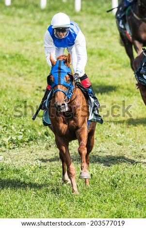STOCKHOLM - JUNE 6: Jockey after a curve at the Nationaldags Galoppen in Gardet. June 6, 2014 in Stockholm, Sweden. - stock photo