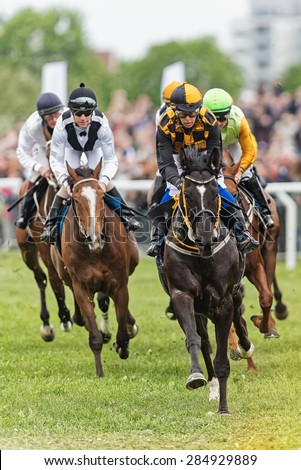 STOCKHOLM - JUNE 6: Jockeys and horses running towards the camera at the Nationaldags Galoppen at Gardet. June 6, 2015 in Stockholm, Sweden. - stock photo