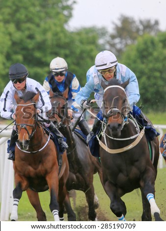STOCKHOLM - JUNE 06: Three jockeys on race horses competing hard at the Nationaldags Galoppen at Gardet. June 6, 2015 in Stockholm - stock photo