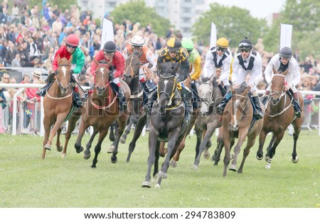STOCKHOLM - JUNE 06: Tough race between the race horses in the first curve at the Nationaldags Galoppen at Gardet. June 6, 2015 in Stockholm - stock photo