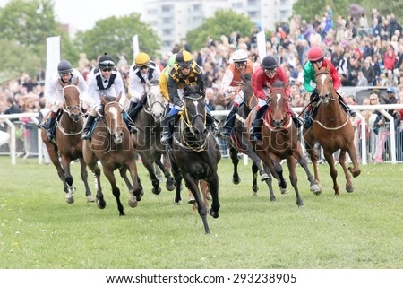 STOCKHOLM - JUNE 06: Tough race between the race horses in the last curve at the Nationaldags Galoppen at Gardet. June 6, 2015 in Stockholm - stock photo