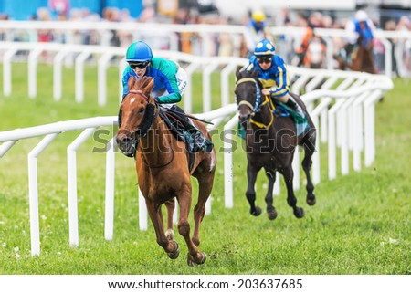 STOCKHOLM - JUNE 6: Two jockeys out of the fourth curve at the Nationaldags Galoppen in Gardet. June 6, 2014 in Stockholm, Sweden. - stock photo