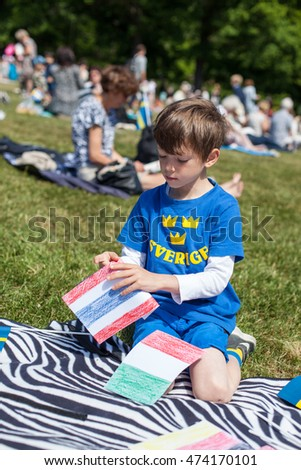 STOCKHOLM, JUNE 6, 2016, young boy with mixed ethnicity sitting on a picnic blanket fixing flags to wave on Sweden´s National Day celebrated in a park on a sunny summer day.
