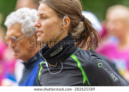 STOCKHOLM - MAY 30: Closeup of a woman with earplugs in ASICS Stockholm Marathon 2015. May 30, 2015 in Stockholm, Sweden. Runners from 101 nations were registered in 2015