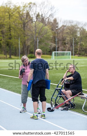 STOCKHOLM, MAY 2016, disabled, older woman getting some boxing exercise while friend sit and watch her punch at the teacher on an overcast day. - stock photo