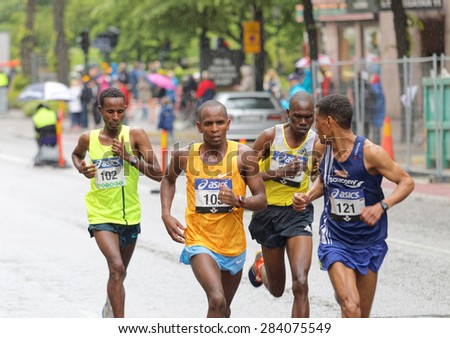 STOCKHOLM - MAY 30, 2015: Four male runners in the lead after 15 km of the the ASICS Stockholm Marathon event May 30, 2015 in Stockholm, Sweden. Yekeber Bayabel (102) will later win the race. - stock photo