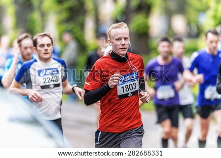 STOCKHOLM - MAY 30: Running man in red in a lush area at ASICS Stockholm Marathon 2015. May 30, 2015 in Stockholm, Sweden. Runners from 101 nations were registered in 2015 - stock photo