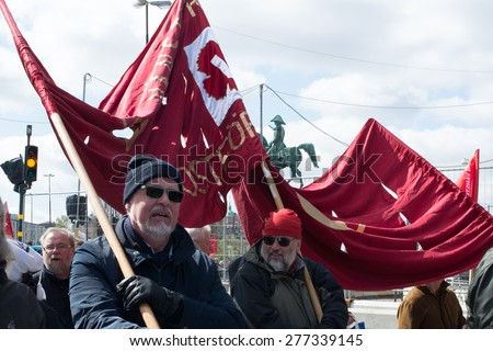Stockholm, May 1, 2014 - Supporters of the Swedish Left Party (Vansterpartiet) Holding a Red Banner and Marching under the Bronze Statue of Karl Johan during the Traditional May First Demonstration - stock photo