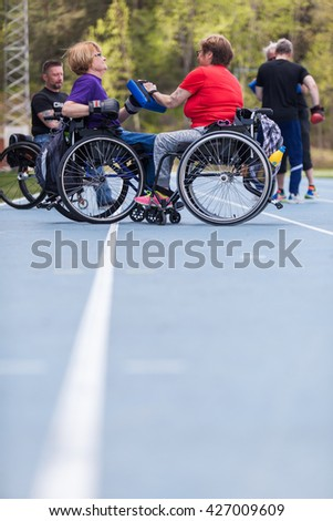 STOCKHOLM, MAY 2016, two disabled women in wheelchairs doing boxing as training exercise with two men in the background doing the same, at the sport center Boson. - stock photo