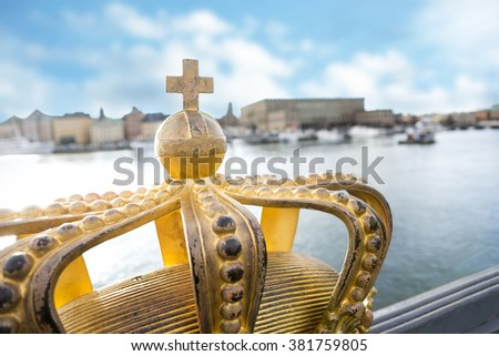 Stockholm old town with royal palace and golden crown on skeppsholmen bridge in foreground - stock photo