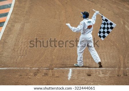 STOCKHOLM - SEPT 26, 2015: Referee with a chequered flag at the finish line at TEGERA Stockholm FIM Speedway Grand Prix at Friends Arena in Stockholm. - stock photo