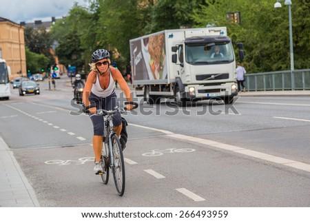 STOCKHOLM - SEPTEMBER 8: Bicyclist on street in Stockholm, Sweden on September 8, 2014. Bicycle is popular ecological transport  in Stockholm. - stock photo