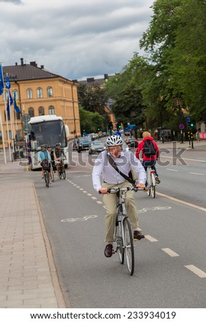 STOCKHOLM - SEPTEMBER 8: Bicyclists on street in Stockholm, Sweden on September 8, 2014. Bicycle is popular ecological transport and about 150 thousand people regularly use bicycles for transportation - stock photo
