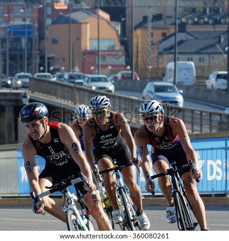 STOCKHOLM, SWEDEN - AUG 23, 2015: Four triathlon cyclist is a shape curve, cars in the background in the Men's ITU World Triathlon series event August 23, 2015 in Stockholm, Sweden - stock photo