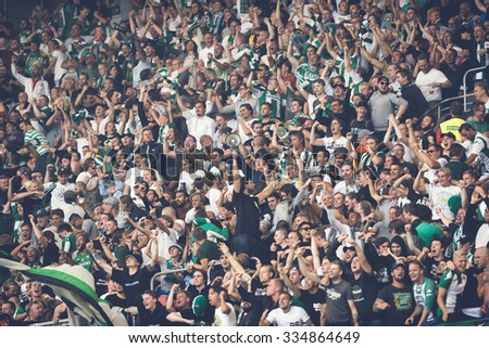 STOCKHOLM, SWEDEN - AUG 24, 2015: The fans of Hammarby after a goal in the soccer game the rivals Djurgarden and Hammarby at Tele2 arena. - stock photo
