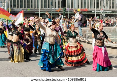 STOCKHOLM, SWEDEN - AUGUST 4: Colorful group of dancing women at Stockholm Pride Parade on August 4, 2012 in Stockholm which attracts an estimated 50000 participants and 500000 spectators. - stock photo