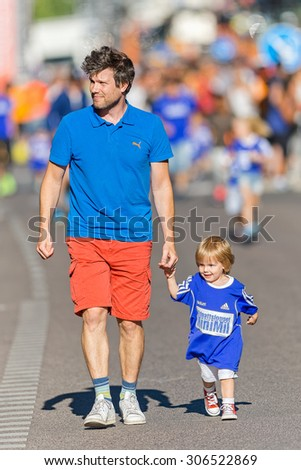 STOCKHOLM, SWEDEN - AUGUST 15, 2015: Dad keeping pace with his kid at the Minimil for the youngest runners at Midnattsloppet. The track is 300 meters and the runners are aged 2-8 years. - stock photo