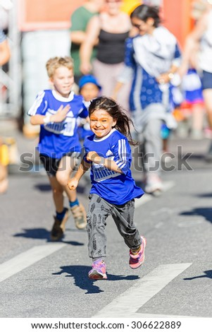 STOCKHOLM, SWEDEN - AUGUST 15, 2015: Energetic smiling young girl at the Minimil for the youngest runners at Midnattsloppet. The track is 300 meters and the runners are aged 2-8 years. - stock photo