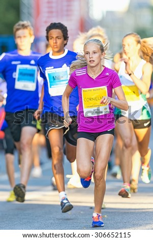 STOCKHOLM, SWEDEN - AUGUST 15, 2015: Girl leading after the start at Lilla Midnattsloppet for aged 15. The track is 1775 meters and the runners are aged 8-15 years. - stock photo