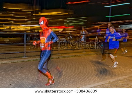 STOCKHOLM, SWEDEN - AUGUST 15, 2015: Man in the mascerade section in spiderman costume on the streets of Soder at Midnattsloppet or the Midnight run. - stock photo