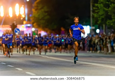 STOCKHOLM, SWEDEN - AUGUST 15, 2015: Runner taking the lead just after the start at Midnattsloppet or the Midnight run. The track is 10 km and goes thru the streets of Stockholm. - stock photo