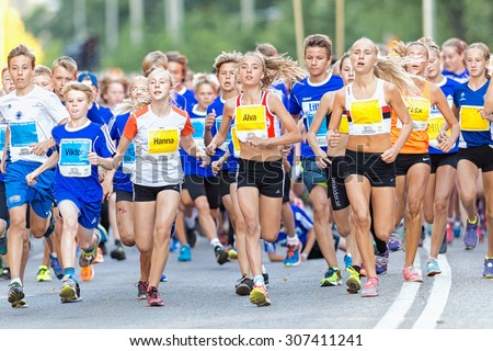 STOCKHOLM, SWEDEN - AUGUST 15, 2015: Runners just after the start at Lilla Midnattsloppet for runners aged 13. The track is 1775 meters and the runners are aged 8-15 years. - stock photo