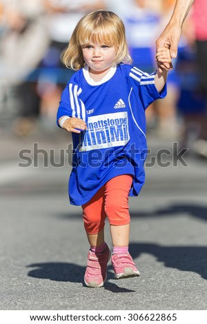 STOCKHOLM, SWEDEN - AUGUST 15, 2015: Small girl running hand in hand with father at the Minimil for the youngest runners at Midnattsloppet. The track is 300 meters and the runners are aged 2-8 years. - stock photo