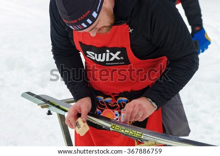 STOCKHOLM, SWEDEN - JAN 24, 2016: Waxing skis at the event Ski Marathon in nordic skiing classic style. - stock photo