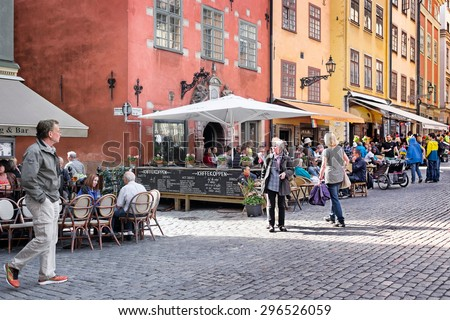 STOCKHOLM, SWEDEN-July 9, 2015: Busy sidewalk cafes in the picturesque historic neighborhood of Gamla Stan. The area is a popular destination for visitors of all ages. - stock photo