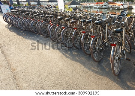 STOCKHOLM, SWEDEN - JULY 30, 2014: Row of city parked bicycles bikes for rent on sidewalk. Bike Bicycle Parking In European City - stock photo