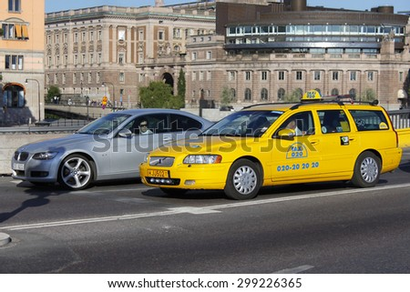 STOCKHOLM, SWEDEN - JULY 7, 2010: Taxi car Volvo V70 and BMW 3-series with their drivers inside are waiting for traffic light on the cross road.