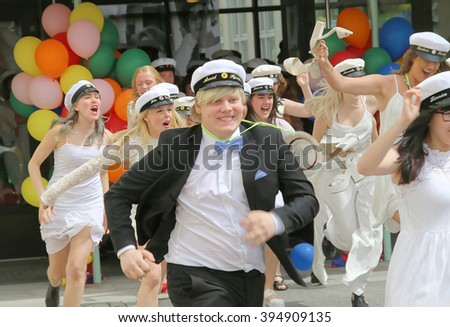 STOCKHOLM, SWEDEN - JUN 10, 2015: Group of happy teenagers wearing graduation caps running out from school after graduation from the high school Globala gymnasiet, June 10, 2015, Stockholm, Sweden - stock photo