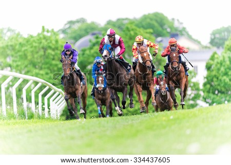 STOCKHOLM, SWEDEN - JUN 6, 2015: Horses with jockeys out of a curve in fast pace at Nationaldagsgaloppen at Gardet. - stock photo