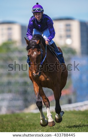 STOCKHOLM, SWEDEN - JUNE 6, 2016: Closeup of a jockey and race horse at the Nationaldags Galoppen at Gardet with city buildings in background.