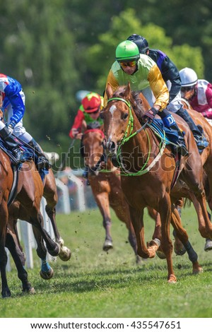 STOCKHOLM, SWEDEN - JUNE 6, 2016: Closeup of jockey and race horse at the Nationaldags Galoppen at Gardet with lush forest behind.