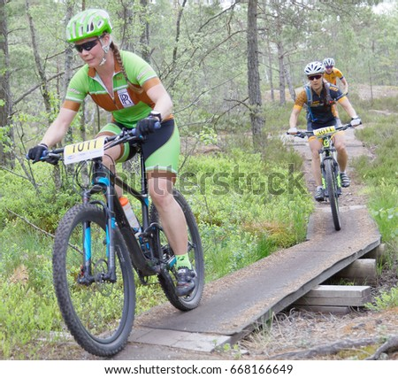 STOCKHOLM, SWEDEN - JUNE 11, 2017: Female mountain bike cyclist in the forest cycling over a bridge in the forest at Lida Loop Mountain bike Race. June 11, 2017 in Stockholm, Sweden
