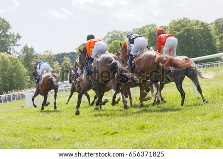 STOCKHOLM, SWEDEN - JUNE 06, 2017: Side, rear  view of jockeys riding race horses in a curve at Nationaldags Galoppen at Gardet. June 6, 2017 in Stockholm, Sweden