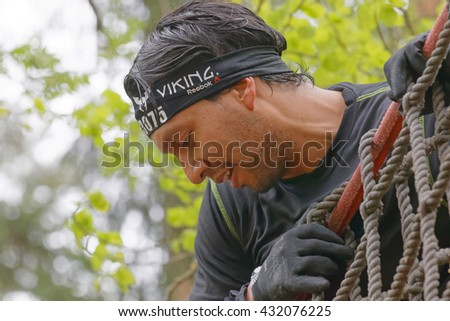STOCKHOLM, SWEDEN - MAY 14, 2016: Closeup of a man climbing up a net in the obstacle race Tough Viking Event in Sweden, May 14, 2016