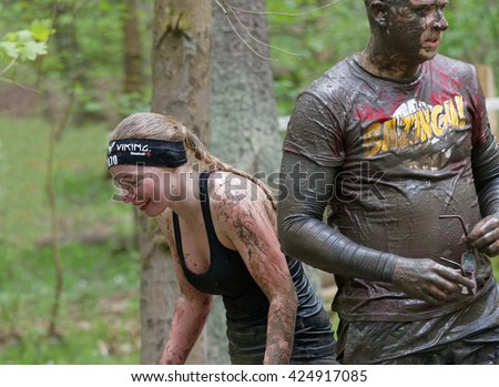 STOCKHOLM, SWEDEN - MAY 14, 2016: Girl and man covered with mud in the obstacle race Tough Viking Event in Sweden, April 14, 2016