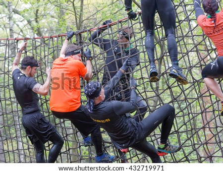 STOCKHOLM, SWEDEN - MAY 14, 2016: Group of men climbing up a net in the obstacle race Tough Viking Event in Sweden, May 14, 2016