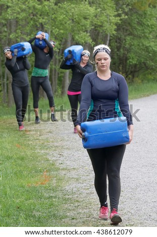 STOCKHOLM, SWEDEN - MAY 14, 2016: Group of woman and men carry a heavy water can in the forest in the obstacle race Tough Viking Event in Sweden, May 14, 2016