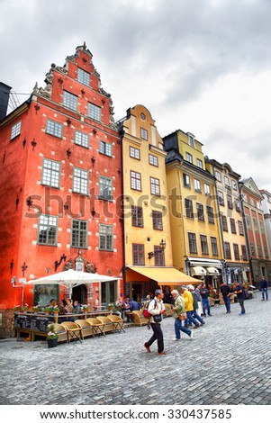 STOCKHOLM, SWEDEN - May 20, 2015: Tourists walking near the most famous houses on Stortorget square in Stockholm - stock photo