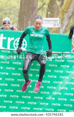 STOCKHOLM, SWEDEN - MAY 14, 2016: Woman jumping out of a tank of ice cold water in the Ice cube obstacle in the obstacle race Tough Viking Event in Sweden, May 14, 2016